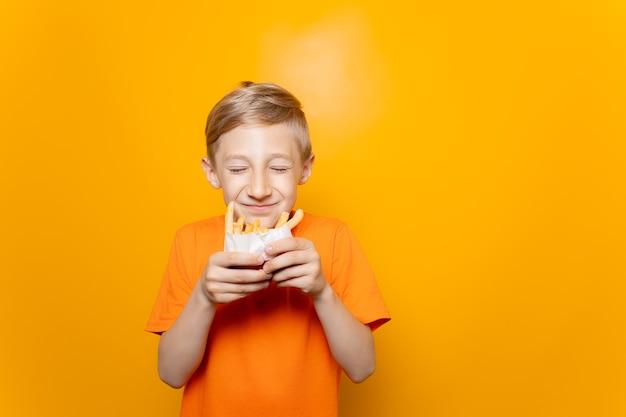 Een jongen in een oranje t-shirt houdt een zak gefrituurde aardappelen voor zich en snuffelt eraan met zijn ogen dicht