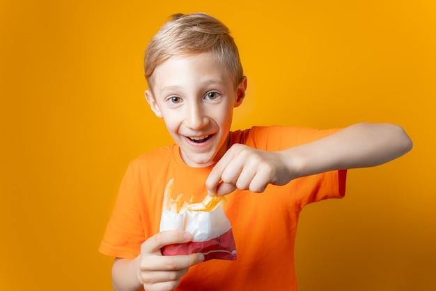 Een jongen in een oranje t-shirt houdt een zak gefrituurde aardappelen voor zich
