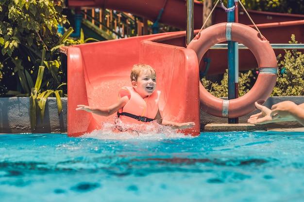 Een jongen in een reddingsvest glijdt van een glijbaan in een waterpark.