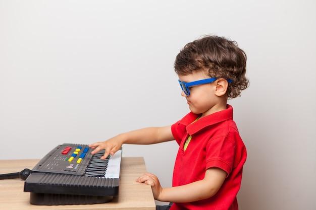 Een jongen in een rood t-shirt en blauwe zonnebril speelt een speelgoedsynthesizer, een piano. al op jonge leeftijd leren en wennen aan muziekinstrumenten