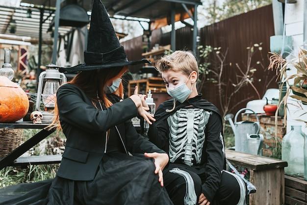 Een jongen in een skeletkostuum en een meisje in een heksenkostuum met een beschermend gezichtsmasker op een halloween-feest in een nieuwe realiteit als gevolg van de covid-pandemie