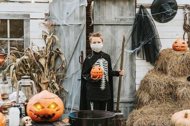 Een jongen in een skeletkostuum met een beschermend gezichtsmasker op een halloween-feest in een nieuwe realiteit vanwege de covid-pandemie