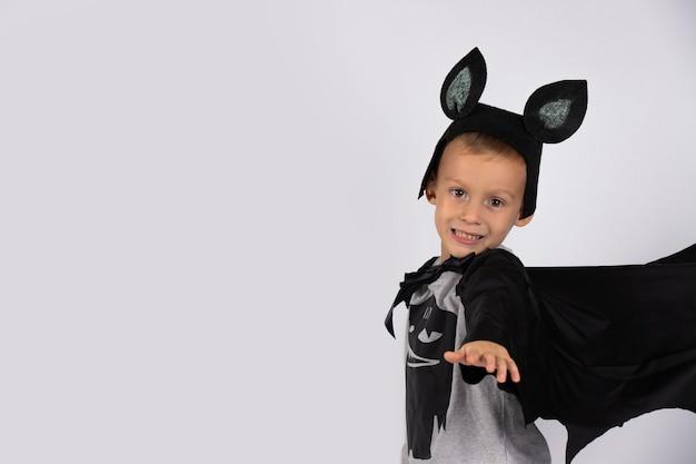 Een jongen in een vleermuiskostuum, met schattige oortjes, strekte zijn hand naar de camera, de vleugels open, vliegt omhoog.