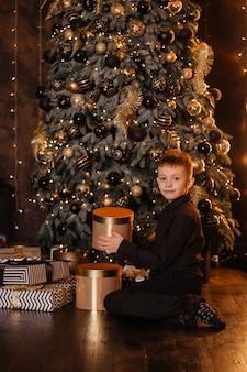Een jongen in een zwart shirt bij de kerstboom opent een nieuwjaarscadeau