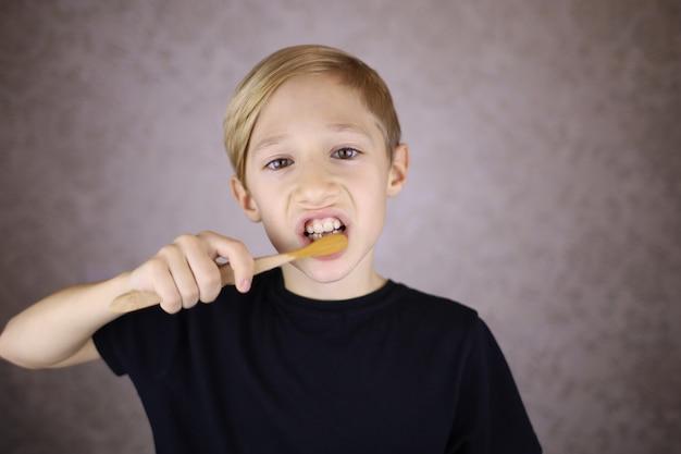 Een jongen in een zwarte t-shirt poetst zijn tanden