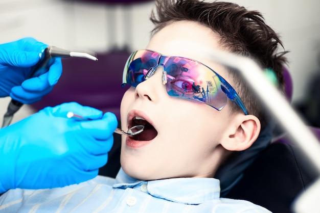 Een jongen in speciale bril in de stoel van de tandarts