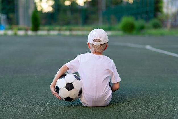 Een jongen in sportkleding zittend op een groen gazon op een voetbalveld met een voetbal terug, achteraanzicht