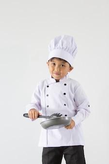 Een jongen in uniform chef