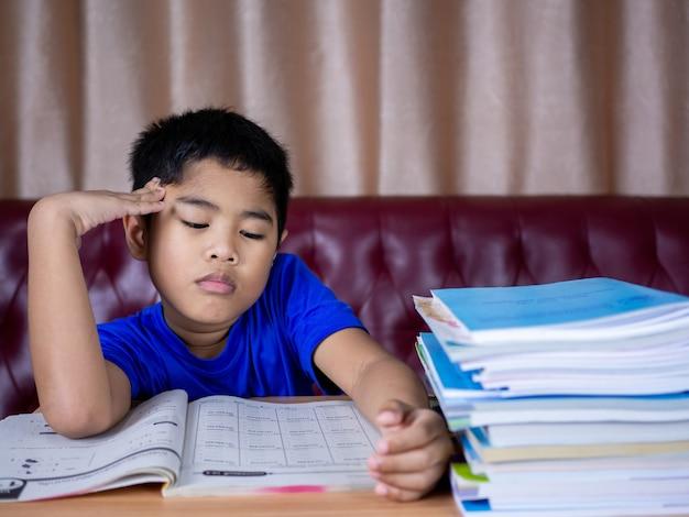 Een jongen is moe van het lezen van een boek op een houten tafel. met een stapel boeken ernaast de achtergrond is een rode bank en crèmekleurige gordijnen.