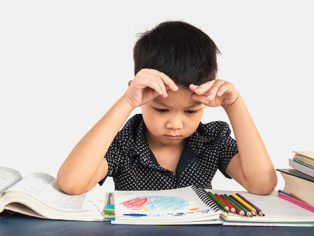 Een jongen is ongelukkig huiswerk maken