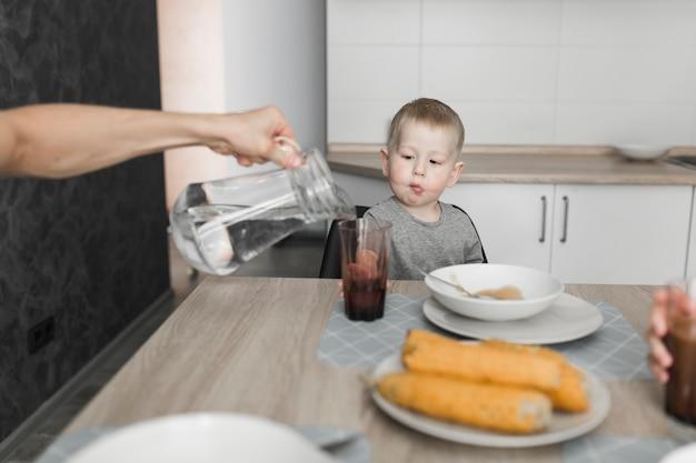 Een jongen kijkt naar een persoon gieten water in het glas bij het ontbijt