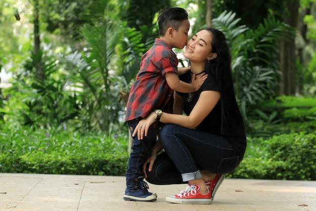 Een jongen kuste de wangen van zijn moeder liefdevol