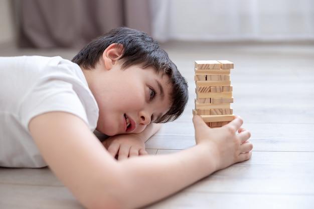 Een jongen ligt op de grond in de kamer en speelt het spel van torenhouten blokken. gezinsbordspellen
