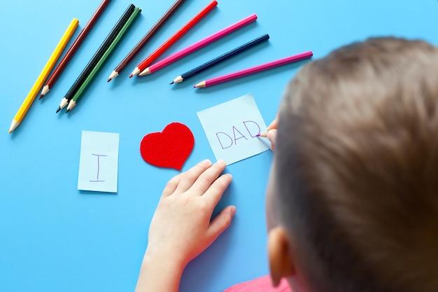 Een jongen maakt een cadeau voor vaderdag