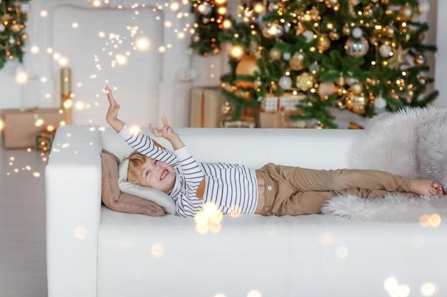 Een jongen met blond haar tegen de achtergrond van een kerstboom ligt op een bank en droomt van het beste kerstcadeau