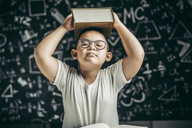 Een jongen met bril studeerde en legde een boek op zijn hoofd in de klas.