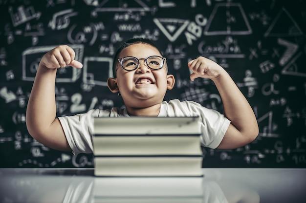 Een jongen met bril zit in de studeerkamer en met beide armen loodrecht