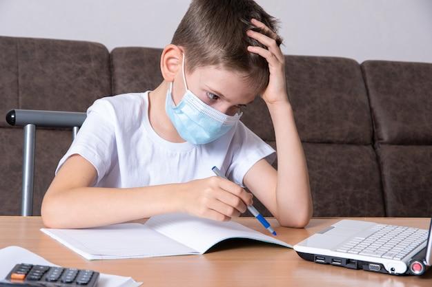 Een jongen met een beschermend masker op zijn gezicht studeert online, schrijft informatie in een notitieboekje, zittend aan een bureau voor een laptop. online onderwijsconcept, afstandsonderwijs