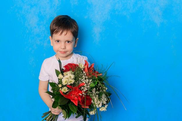 Een jongen met een boeket op een blauwe achtergrond.