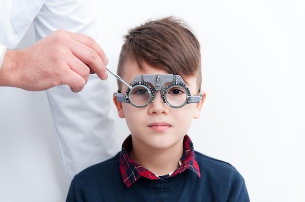 Een jongen met een bril controleert oogzicht bij een oogarts