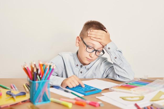 Een jongen met een bril houdt zich bezig met lessen