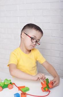 Een jongen met een bril met het syndroom van down zit aan een tafel en speelt met speelgoed