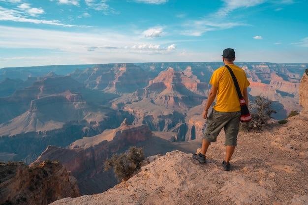 Een jongen met een geel overhemd bij zonsondergang op het mojave point in grand canyon