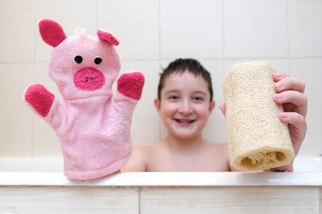 Een jongen met een grappig gezicht zit in een badkuip en toont luffa en handpop washandje close-up.
