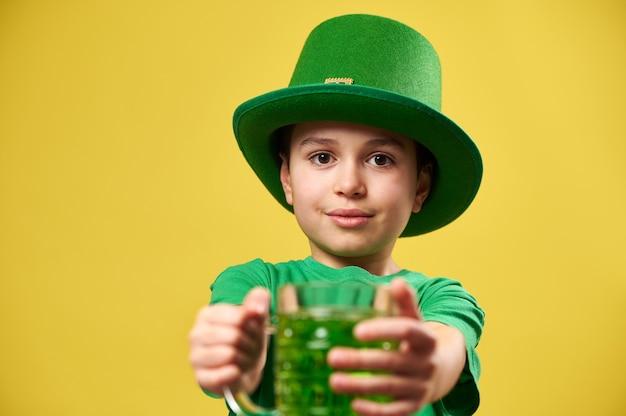 Een jongen met een groene kabouterhoed houdt een glas groen drankje vast en houdt het voor zich uit naar de camera