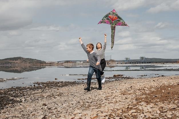 Een jongen met een hengel is aan het vissen, zittend aan de oever van de rivier. een knappe jongen in een gestreept vest zit met een hengel in zijn handen