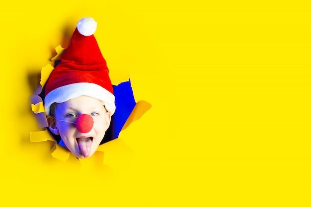 Een jongen met een kerstmuts en de neus van een clown toont zijn tong uit een gat in de gele papieren achtergrond