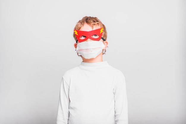 Een jongen met een leuk superheldmasker om zichzelf te beschermen tegen de virale infecties van de ziekte.