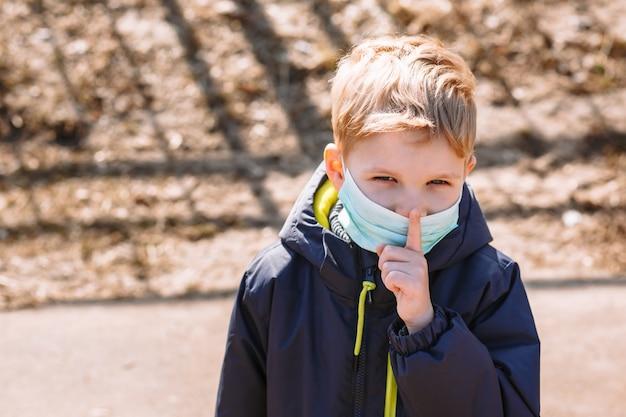 Een jongen met een medisch masker maakt een shhh-gebaar
