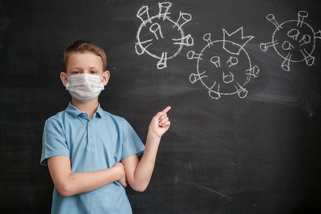 Een jongen met een medisch masker wijst naar een krijttekening van het coronavirus op een zwart schoolbord. het concept van een pandemische covid-19