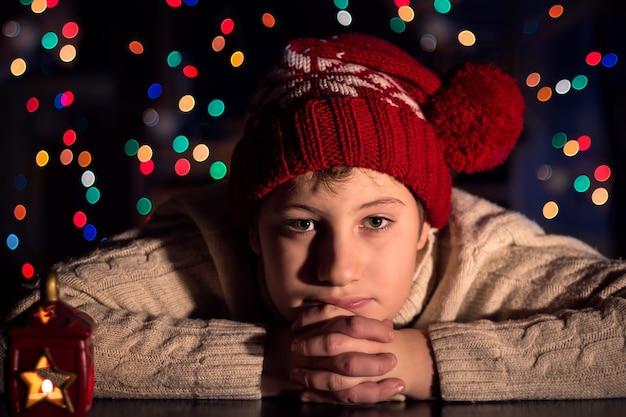Een jongen met een rode pet in afwachting van kerstmis