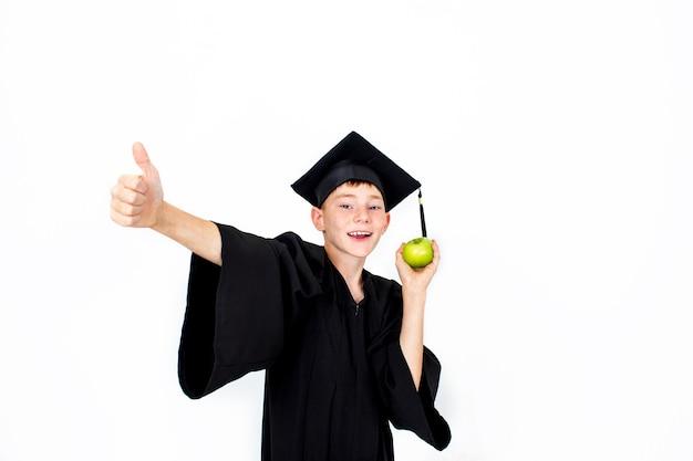 Een jongen met een studentenhoed met een appel in zijn hand. kennis, opleiding en succesvolle carrière.