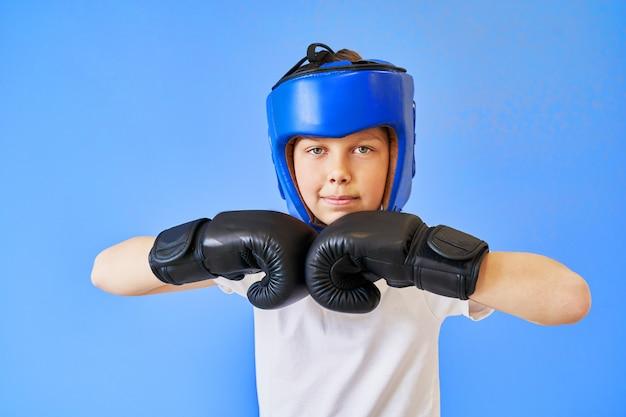 Een jongen met groene ogen die een in dozen doende helm en handschoenen op een blauwe achtergrond dragen