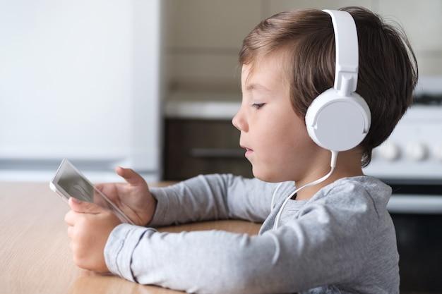 Een jongen met koptelefoon en een tablet zit aan een tafel in de keuken.