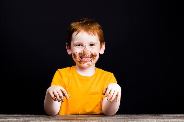 Een jongen met rood haar bedekt met chocolade besmeurde gezicht en handen
