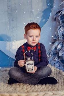Een jongen met rood haar en sproeten op een blauwe achtergrond en een met sneeuw bedekte boom