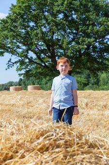 Een jongen met rood haar loopt in een veld met stoppels en stapels stro van tarwe