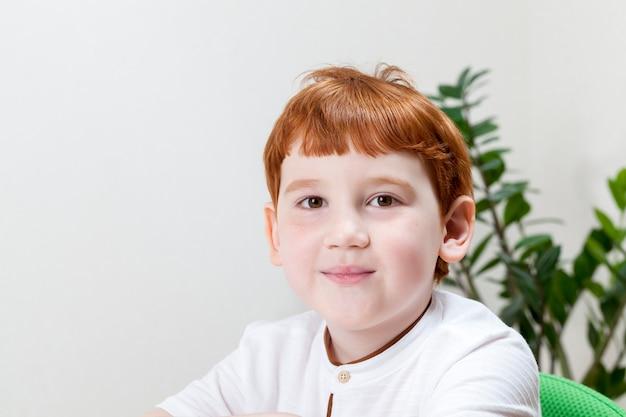 Een jongen met rood haar tijdens het studeren of werken, een jongen tekent met kleurpotloden op een stuk papier