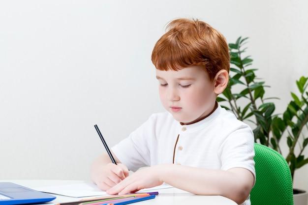 Een jongen met rood haar tijdens het studeren of werken