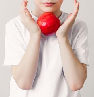 Een jongen met rustige emoties in een wit t-shirt heeft een appel in zijn handen. verticale foto