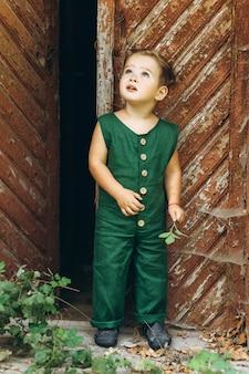 Een jongen met wit haar in een groene combinatie speelt naast de houten oude deur