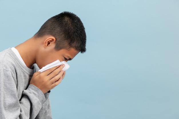 Een jongen niest in weefsel en voelt zich ziek op de blauwe muur.
