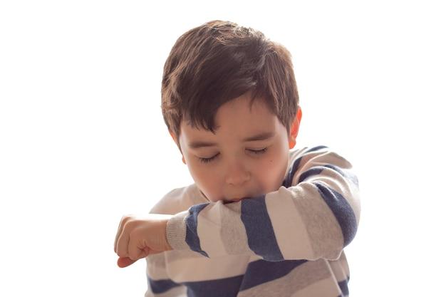 Een jongen niest of hoest in zijn elleboog op wit.
