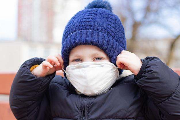 Een jongen op de speelplaats in een masker. gezondheid. coronavirus. medisch masker op het gezicht van het kind. veiligheid . longontsteking en griep. ademhalingsbescherming.