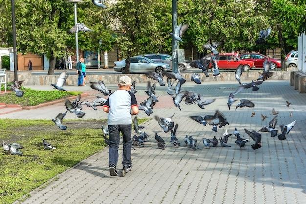 Een jongen op een scooter jaagt een zwerm duiven na