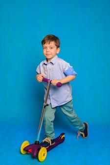 Een jongen op een scooter op een blauwe achtergrond een artikel over kinderscooters a